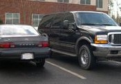 A Ford Excursion Sport Utility Vehicle next to a Toyota Camry